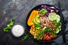 Buddha-Schüsselteller mit Naturreis, Avocado, Pfeffer, Tomate, Gurke, Rotkohl, Kichererbse, frischem Kopfsalatsalat und Walnüssen stockbild