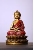 Buddha Sculpture. Gold and red Buddha figure meditating Stock Photo