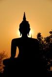 Buddha sculpture and evening sunlight. Contour sunlight behind Buddha sculpture with trees Royalty Free Stock Photography