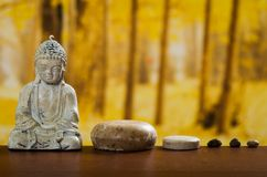 Buddha sculpture with soaps and stones spa concept Stock Photos