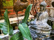 Buddha sculpture with some leaves. A religious sculpture of Buddha with some green leaves in from of the statue Royalty Free Stock Photography