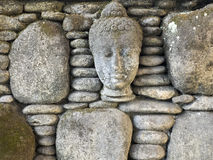 Buddha sculture on round stone wall. Close up Stock Images