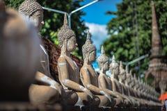 Buddha sitter rad tillsammans arkivbilder