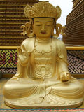 Buddha. Sitting in the Lotus position on the background of the mausoleum Royalty Free Stock Image
