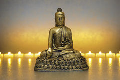 Buddha sitting in meditation. With line of candle lights Stock Image