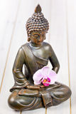 Buddha. Sitting buddha with pink orchid Royalty Free Stock Images