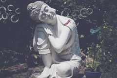 Buddha sitting on a trunk with bubbles Stock Photography