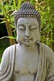 Buddha skulptur med bambu lämnar Royaltyfria Bilder
