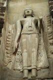 buddha som ser stenen upp väggen Arkivbilder