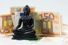 Buddha sorrounded by money Stock Images