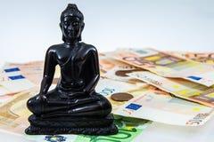 Buddha sorrounded by money Royalty Free Stock Photo