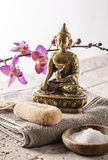 Buddha for spirituality at home spa. Spa and spirituality concept - Buddha,bath salt and exfoliation accessories with orchids on pure stone background for soft royalty free stock photography