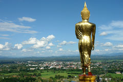 Buddha standing golden. Sculpture gold buddha facing standing city from nan in thailand, blue sky background stock photography
