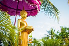 The Buddha stands under the purple umbrella in nature Prepared f. Or people are pour water of Songkran festival day stock photos