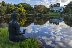 Buddha-Statue über dem Schauen von einem See Stockfotos