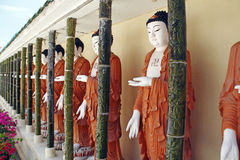 Buddha statue. An image of a row of Buddha statue in brown robe stock photo