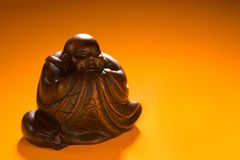Buddha Statue. A small statue of the oriental god Buddha against an orange background stock photography