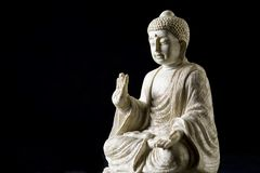 Buddha statue. White buddha statue isolated against black Royalty Free Stock Photography