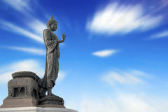 Buddha statue against on blue sky blurred background. Royalty Free Stock Photo