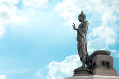 Buddha statue against on blue sky blurred background. Stock Photos