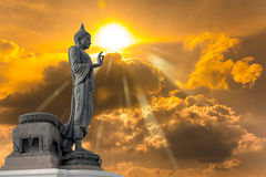 Buddha statue against on Golden sky with sunlight in background. Stock Images