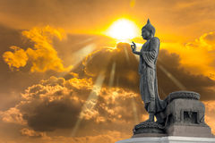 Buddha statue against on Golden sky with sunlight in background. Stock Photo