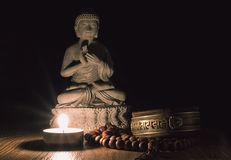 Buddha-Statue auf Bretterboden mit Kerze stockbild