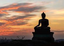 Buddha-Statue auf Sonnenunterganghimmelhintergrund Stockbild
