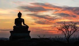 Buddha-Statue auf Sonnenunterganghimmelhintergrund Lizenzfreies Stockbild