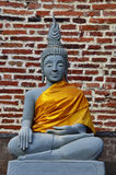 Buddha statue in front of a brickwall Stock Photo
