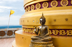 Buddha statue at base of pagoda at hilltop temple Royalty Free Stock Photography