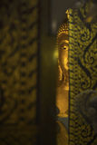 Buddha statue behind temple door. In Thauland royalty free stock image