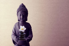 Buddha statue on a beige background with flower Stock Photo