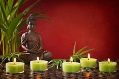 Buddha statue and candles. On a red background stock photos