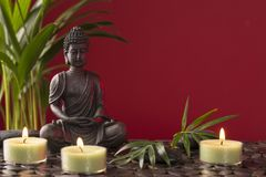 Buddha statue and  candles. On a red background royalty free stock photo