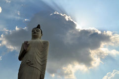 Buddha statue with clouds in Sri Lanka. Rays of sun coming out of a cloud behind a Buddha statue in a temple near Sigiriya, Sri Lanka Stock Image