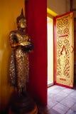 Buddha-Statue, die nahe bei den Türen in einem Tempel steht. Stockfoto