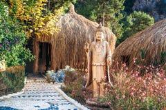 Buddha-Statue draußen mit Hütten im Hintergrund Stockfotografie