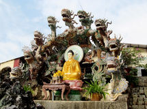 Buddha statue dressid in yellow with dragons stock image