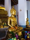 Buddha statue with enormous gold leafs. Royalty Free Stock Photo