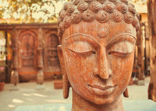 Buddha statue face with closed eyes in calm area of asian town with temples Royalty Free Stock Photo