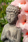 Buddha statue in a flowergarden with pink flowers Stock Images