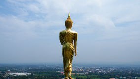 Buddha statue - Golden Buddha on the hill. Buddha - golden Buddha on a hill standing behind, similar to the sky in the sky Stock Image