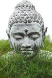 Buddha statue head. Stone Buddha decoration bust in garden grass Stock Photos