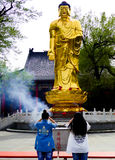 Buddha statue of Jile temple. Two young women worshiping on bended knees a gilded buddha sculpture inside Kek Lok Si Temple Harbin city Heilongjiang province Stock Photography