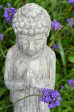 Buddha statue in a lavender garden. Grey Buddha statue in a lavender garden Royalty Free Stock Photos