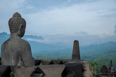 Buddha statue looking over valley. Statue of Buddha at Borobudur temple, Indonesia Stock Photo