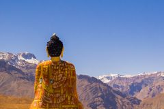 Buddha statue looking at mountains and sky Stock Image