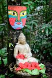 A buddha statue and mask. In a garden Stock Image
