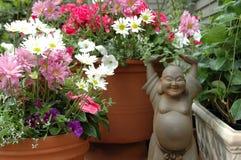 Buddha-Statue mit Blumen Stockfotografie
